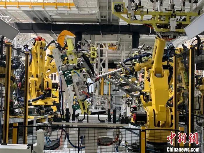 资料图:江西上饶一家新能源电动汽车公司的智慧工厂内,机器人正同时作业。 李韵涵 摄